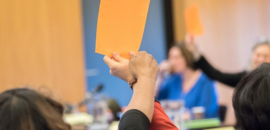 People hold orange paper cards up in the air as a symbol of consensus, affirmation, during a World Council of Churches meeting.