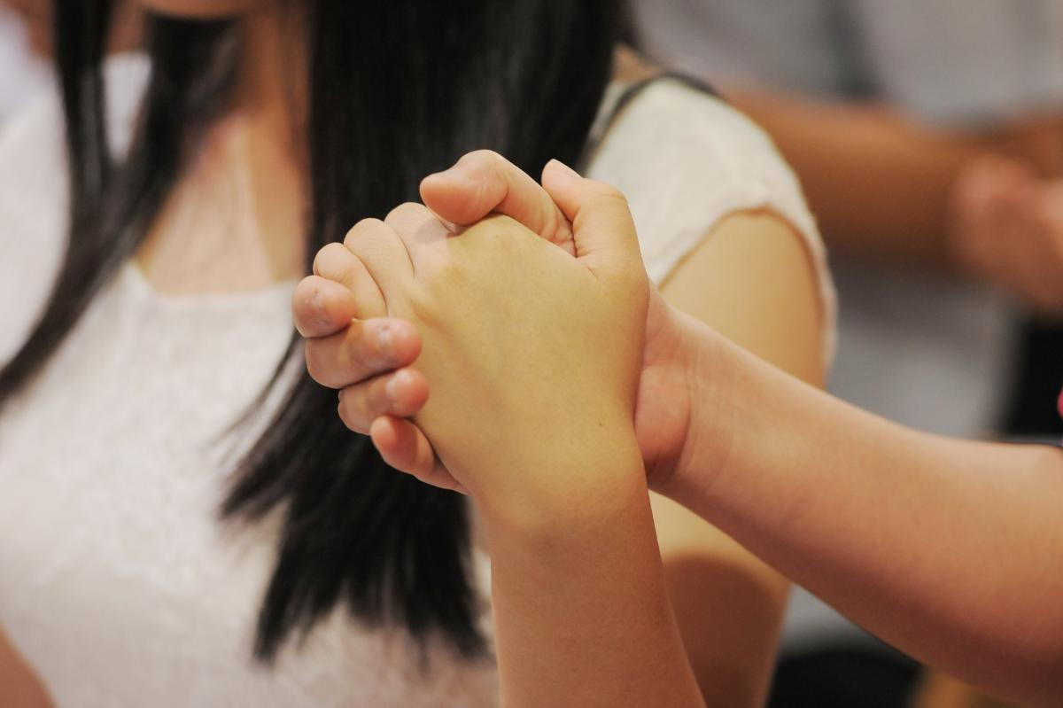 Congregants holding hands in prayer at Holy Family Church Singapore