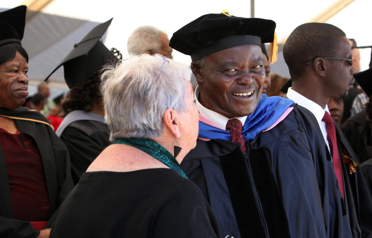 Patrick Matsikenyiri, former AU choir director and author of the Africa University song, greets a member of the Jubilate Choir from the Pacific Northwest Conference during the March 23, 2013, 20th anniversary celebration of Africa University.