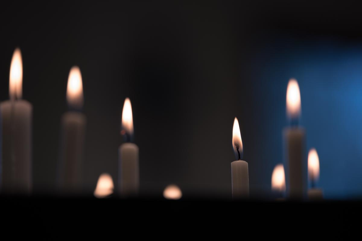 Candles burning in dark room, with blue light in the background