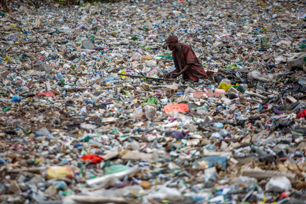 A man retrieves plastic waste in a river in Nairobi, Kenya. Photo: Sean Hawkey
