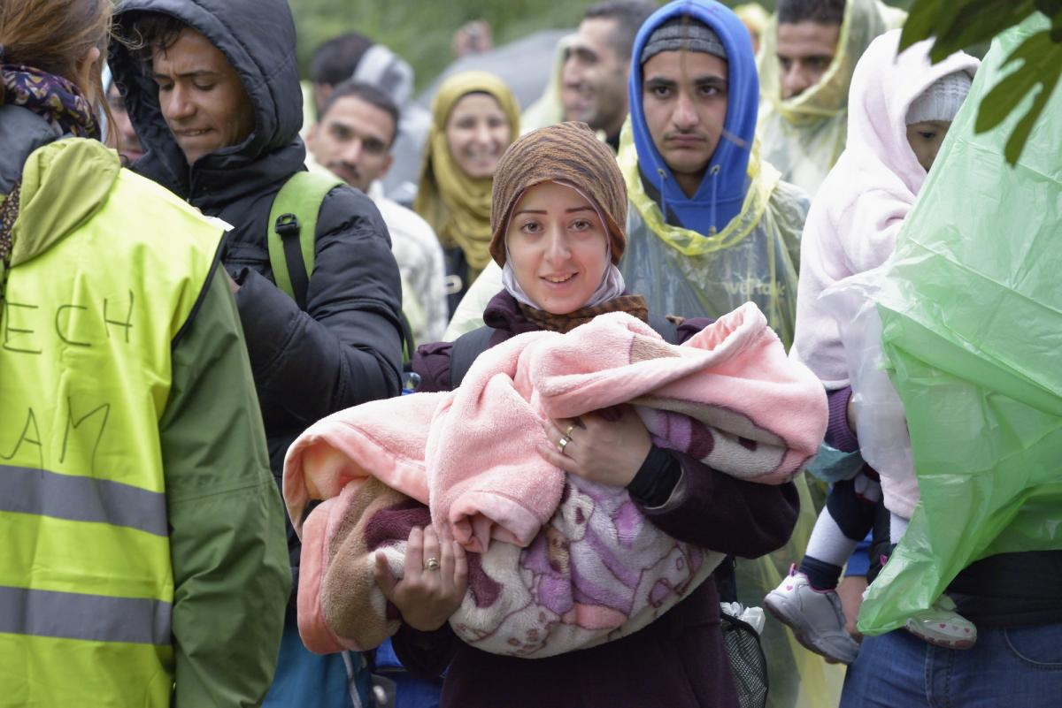 A woman holds a baby in her arms as refugees approach the border of Croatia near the Serbian village of Berkasovo. Photo: Paul Jeffrey/ACT