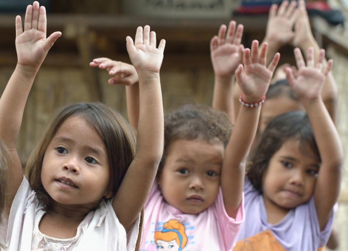 Indigenous children displaced by paramilitary violence exercise at the beginning of a school day in a church compound in Davao, on the southern Philippine island of Mindanao.