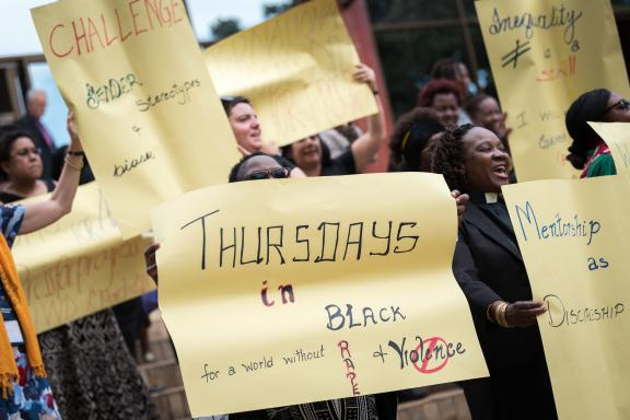 Women marching with Thursdays in Black placards