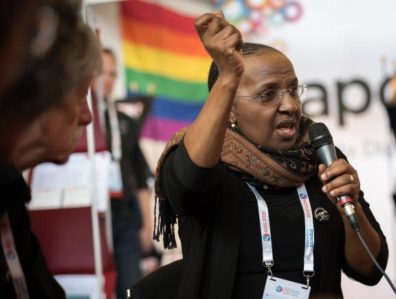 Woman speaks at morning prayer at the AIDS 2018 Interfaith Networking Zone