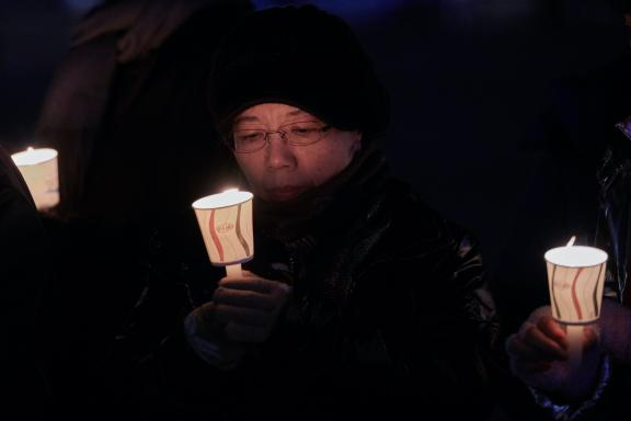 Woman holding candle during Advent peace vigil in South Korea
