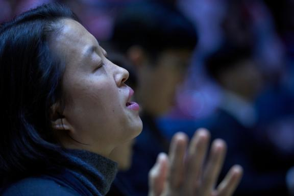 A woman prays during a December 10, 2017, worship celebration in South Korea.