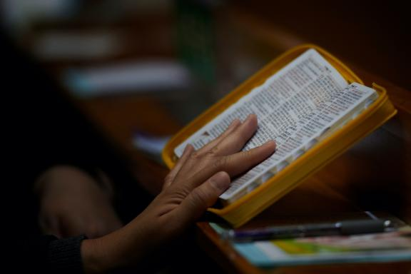 A woman reads the Bible during a worship in South Korea