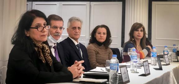 Workshop participants sit around table.