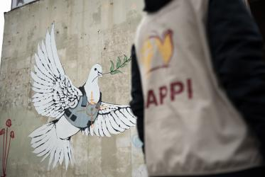 Drawing of a dove carrying an olive branch while wearing a bullet proof vest, on a wall in Bethlehem.