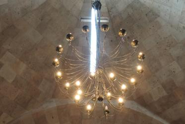 Cross and chandelier in chapel ceiling