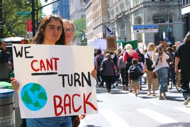 "Youth with ""we can't turn back"" sign for climate"