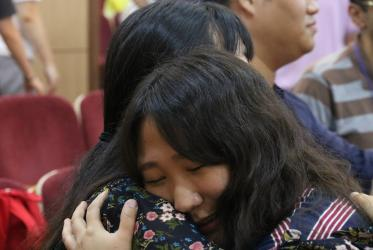 an asian young woman hugs a friend
