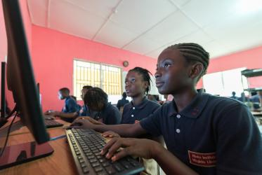 12-year-old Sodah Sackor (right) and 12-year-old Vickey V. Wion (left) study in the computer lab at Ricks Institute, Liberia, 2019..