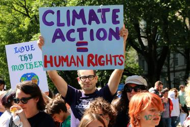 "a man holds a sign that reads ""climate action = human rights"" during a climate march in New York, 2019"