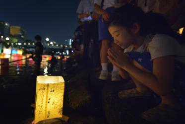 A girl prays after setting a floating candle lantern on the river in Hiroshima, Japan.
