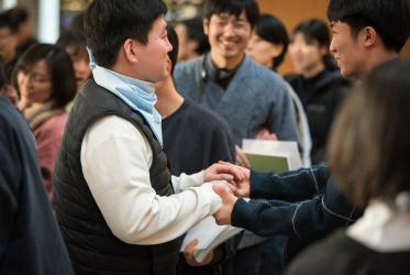 People share a sign of peace with each other at the conclusion of morning prayer in the Ecumenical Centre chapel, as some 75 Korean Christians from the Bargn Nuri Community, Korea, visit the World Council of Churches. Photo: Albin Hillert/WCC