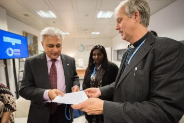Rev. Henrik Grape, moderator of the WCC working group on climate change, hands the interfaith declaration to UNFCCC's deputy executive director Ovais Sarmad. Photo: LWF/Albin Hillert