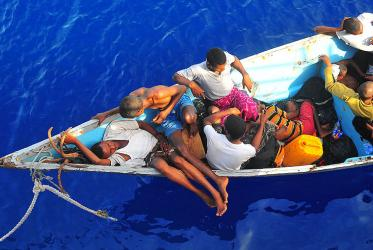 Somali migrants in a disabled skiff wait for assistance.