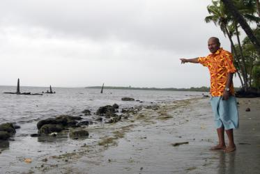 John Dunn indicates where the graveyard of his ancestors was located until 10 years ago, in Togoru. The rise of sea levels has been forcing displacement and adaptation in many parts of Fiji. Photo: Marcelo Schneider/WCC