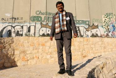 Dinesh Suna by the Separation Wall at Bethlehem on the West Bank. © Peter Kenny/WCC