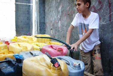 A child is filling jerry cans from a public water supply tap in Gaza, June 2014. © EWN