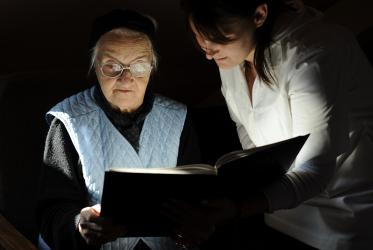 Resident and carer reading the Bible at a home for the elderly in Oradea, Romania. © United Bible Societies/Dag Smemo