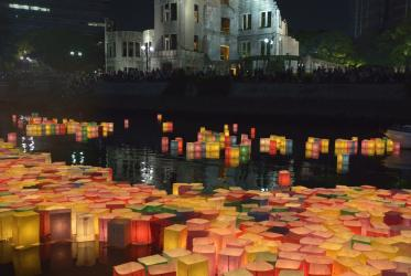 Candle lanterns drift downstream on August 6, 2015, in Hiroshima, Japan, in front of the city's atomic bomb dome. Photo: Paul Jeffrey/WCC