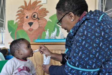 A nurse at the St. Francis Care Centre's Rainbow Cottage for Babies in Johannesburg, South Africa, administers antiretroviral medication to a child living with HIV. Photo: Paul Jeffrey/WCC