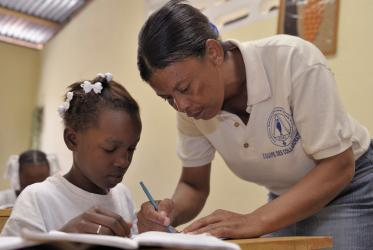 A teacher helps school girl in Port-au-Prince, Haiti. 2011. © ACT/Paul Jeffrey