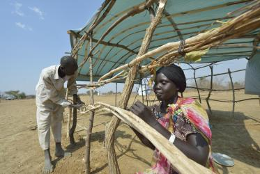 The prolonged conflict in South Sudan has left many displaced over the years. Here, Aluel Yuot ties sticks together as she constructs a shelter in the internally displaced persons camp in Turalei, South Sudan. Photo: Paul Jeffrey/ACT, 2014
