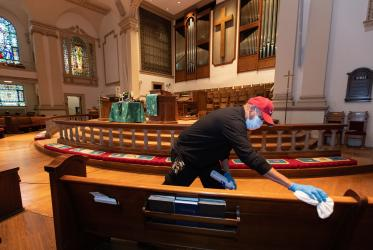 Custodian James Jimmerson disinfects pews to prevent spread of the coronavirus at Belmont United Methodist Church in Nashville, TN, on 10 May, following online worship, which is recorded in the sanctuary. Photo: Mike DuBose/UM News